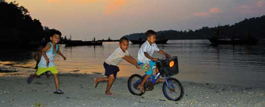 Moken children play on the beach with a bike